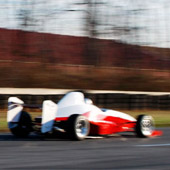 Rear view of the Philly Motor Sports F1000 race car speeding away on the outdoor track