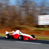 Image of the F1000 race car in motion on an outdoor track with blurred background